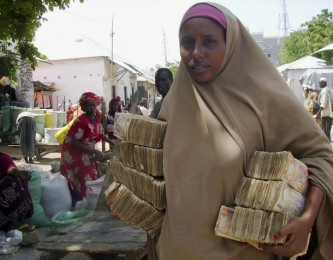 A money changer carries Somali currency at the Bakara open air market in Mogadishu